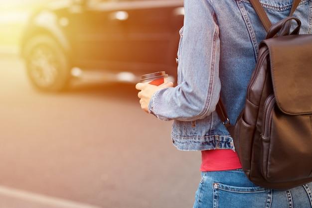 La mano della donna con la tazza di caffè di carta porta via in una via della città Foto Premium