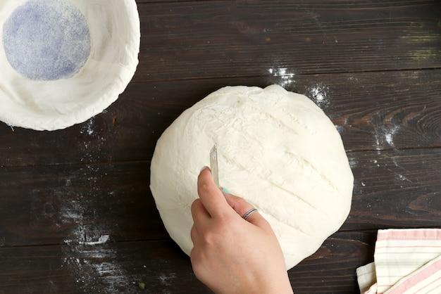 La mano della donna decora appena preparato per cuocere il pane sano casalingo su un fondo scuro di legno. Foto Premium