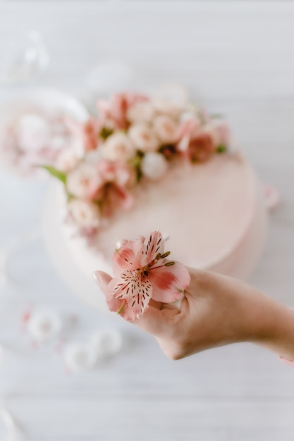 La mano della donna decora la torta di compleanno di nozze rosa con fiori freschi. Foto Premium