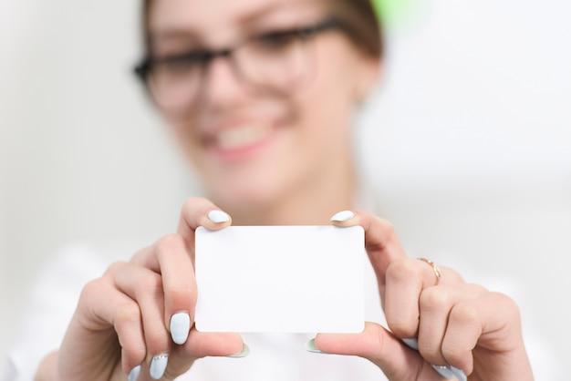 La mano della donna di affari che mostra il biglietto da visita bianco in bianco verso la macchina fotografica Foto Gratuite