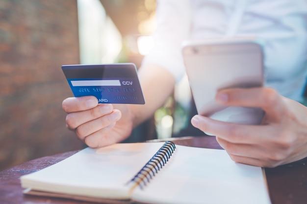 La mano della donna di affari tiene una carta di credito blu e usa i telefoni cellulari. Foto Premium
