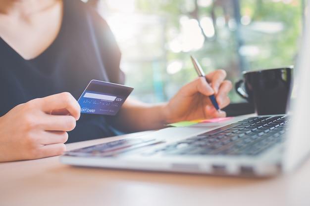 La mano della donna di affari tiene una carta di credito e utilizza un computer portatile per acquistare online. Foto Premium