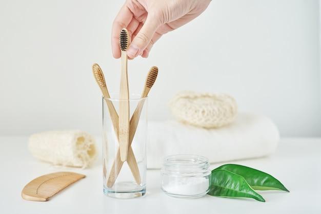 La mano della donna prende lo spazzolino da denti di bambù di legno in un interno del bagno. nessun concetto di plastica a zero rifiuti. spazzolini da denti amichevoli di eco in vetro, asciugamano, polvere di dente e pezzuola per lavare su fondo bianco Foto Premium