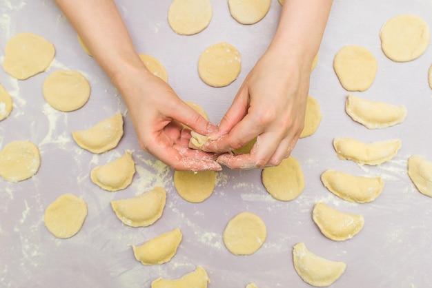 La mano della donna produce ravioli Foto Premium