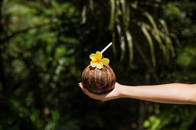 La mano della donna tiene la bevanda della noce di cocco con il fiore giallo su Foto Premium