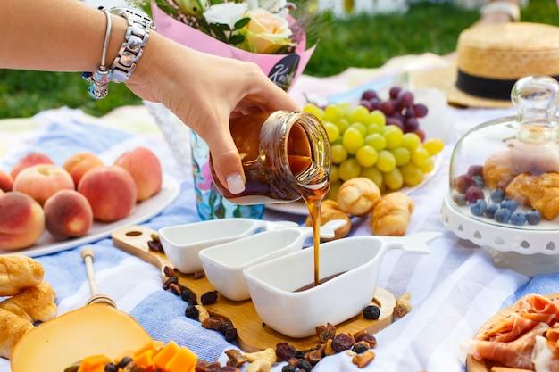La mano della donna versa il miele dalla bottiglia trasparente a sauceboat, alla priorità bassa di picnic di estate Foto Premium