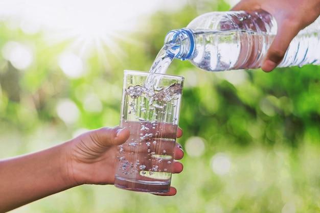 La mano della mamma che versa acqua potabile in una bottiglia di vetro dà un bambino Foto Premium