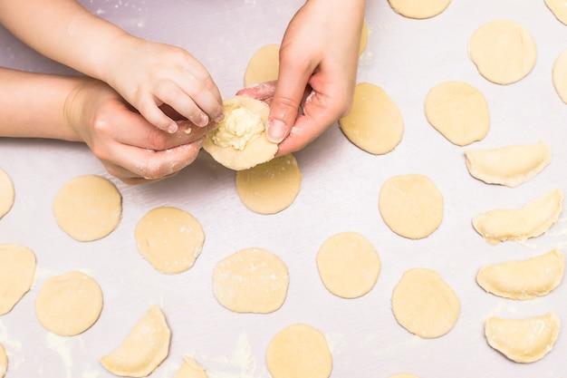 La mano della mamma e del bambino produce i ravioli Foto Premium