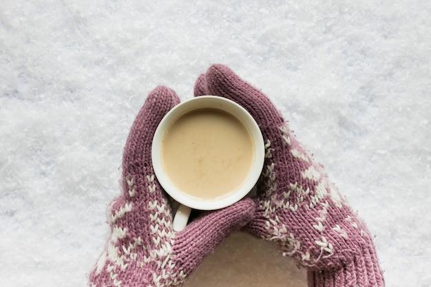 La mano della persona in guanto accogliente che tiene tazza di caffè su terra innevata Foto Gratuite