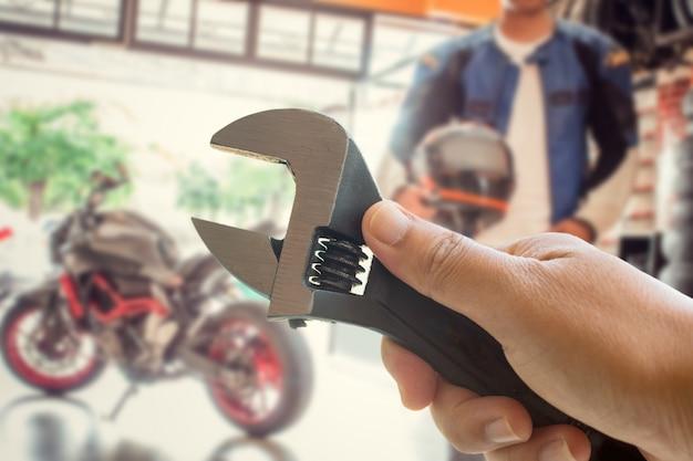 La mano della persona tiene in mano uno strumento di manutenzione per moto. manutenzione prima di guidare Foto Premium