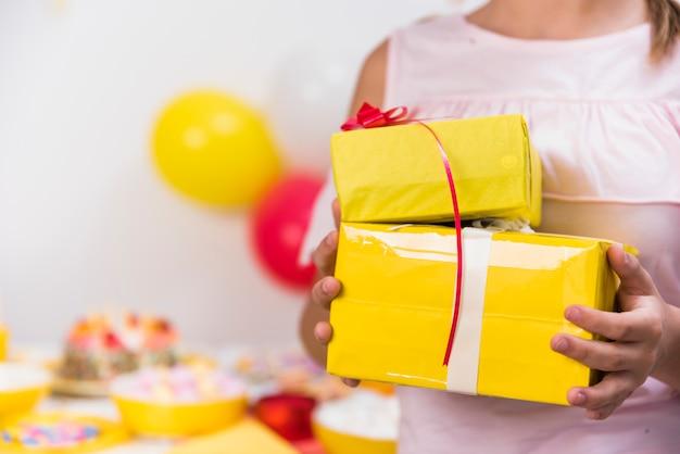 La mano della ragazza che tiene i contenitori di regalo gialli con il nastro rosso Foto Gratuite