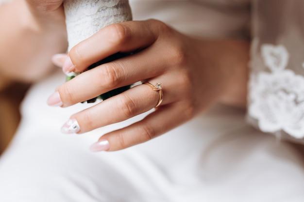 La mano della sposa con un anello di fidanzamento minimalista con un diamante Foto Gratuite