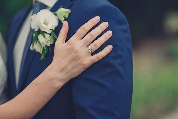 La mano della sposa sta abbracciando il suo sposo Foto Premium