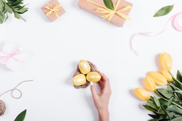 La mano delle donne mette le uova di pasqua gialle in un nido su un tavolo vicino ai tulipani Foto Premium