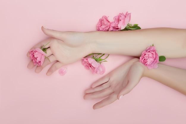 La mano di bellezza di una donna con i fiori rossi si trova sulla tavola, carta rosa Foto Premium