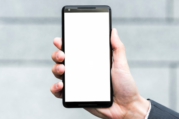 La mano di un uomo d'affari che mostra lo schermo di visualizzazione bianco di uno smartphone contro il contesto vago Foto Gratuite