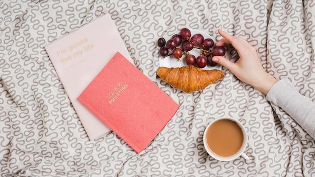 La mano di una donna che tiene l'uva rossa con croissant; tazza di tè e libri sulla tovaglia Foto Gratuite