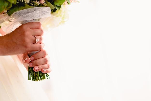 La mano di una donna con la fede nuziale mentre si tiene il suo bouquet, abbondanza di spazio bianco copia. Foto Premium