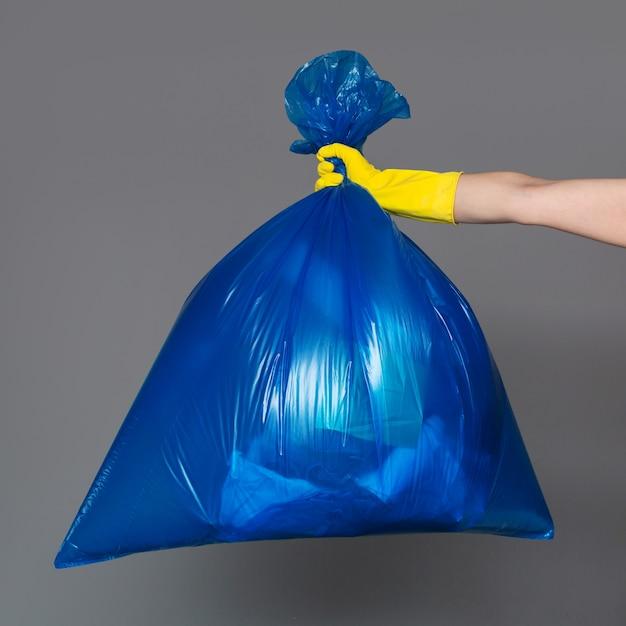 La mano di una donna in un guanto di gomma tiene un sacchetto di plastica blu pieno di immondizia. Foto Premium