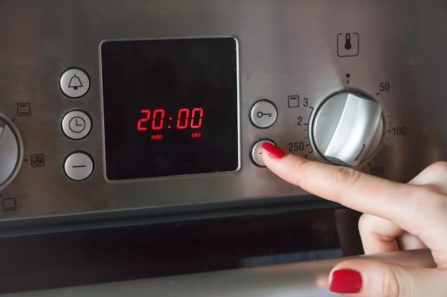 La mano di una donna mette al forno un tempo e una temperatura Foto Premium