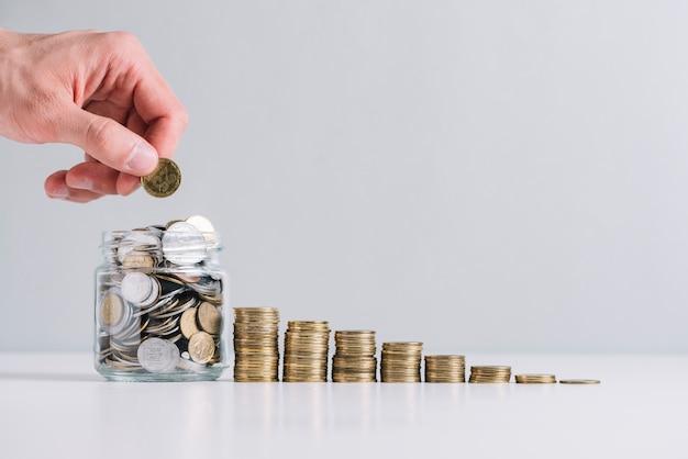 La mano di una persona che mette i soldi in barattolo di vetro vicino a monete impilate diminuendo Foto Gratuite