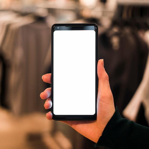 La mano di una persona che tiene il cellulare nel negozio di vestiti Foto Gratuite