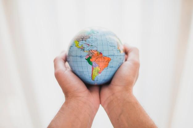 La mano di una persona che tiene un piccolo globo Foto Gratuite