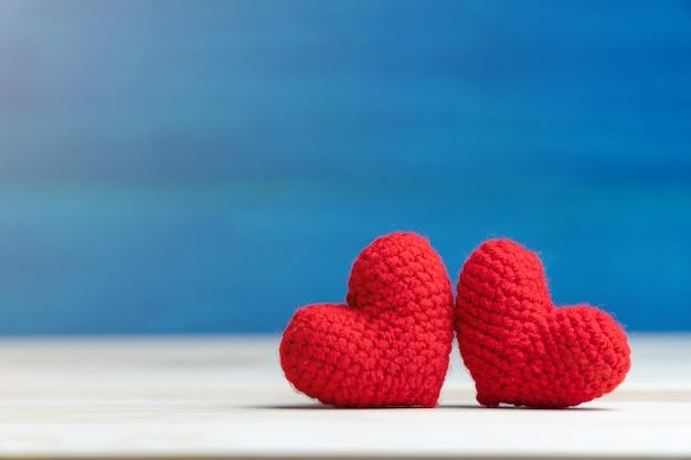 La mano fa il cuore rosso del filato due sulla tavola di legno e sul fondo blu Foto Premium