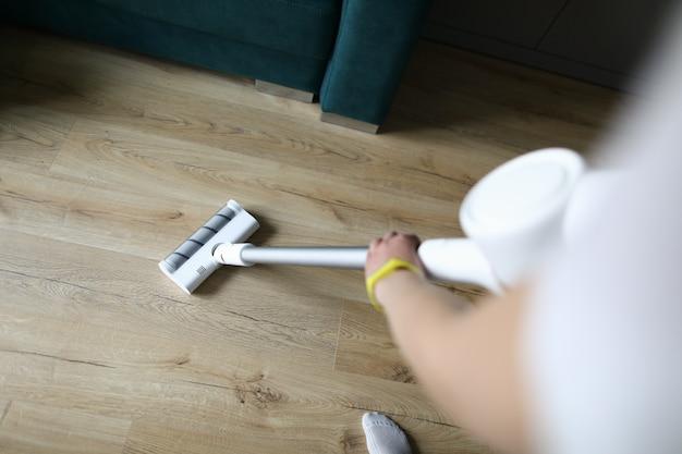 La mano femminile aspira il rivestimento per pavimenti in un appartamento Foto Premium