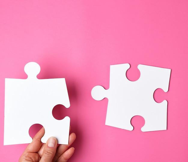 La mano femminile mette i grandi puzzle bianchi su un fondo rosa Foto Premium