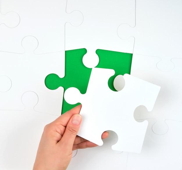 La mano femminile mette i grandi puzzle bianchi Foto Premium