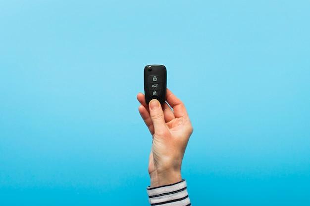 La mano femminile tiene le chiavi dell'automobile su un fondo blu. concept car, noleggio auto, regali, lezioni di guida, patente di guida. Foto Premium