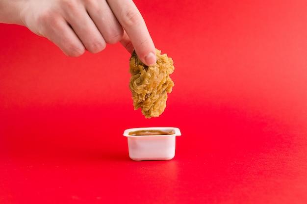La mano femminile tiene le pepite e le immerge in salsa Foto Premium