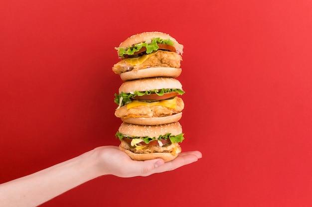 La mano femminile tiene una piramide di tre hamburger Foto Premium