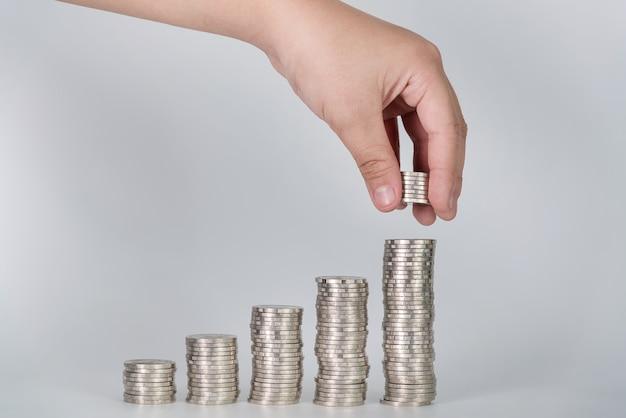 La mano ha messo le monete dei soldi alla pila di monete Foto Premium