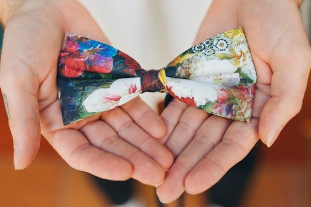 La mano maschile mostrando papillon floreale Foto Gratuite