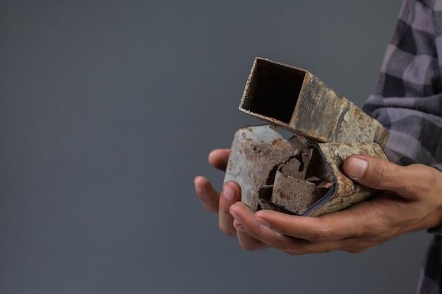 La mano maschile tiene il vecchio rottame di ferro con un grigio. Foto Gratuite