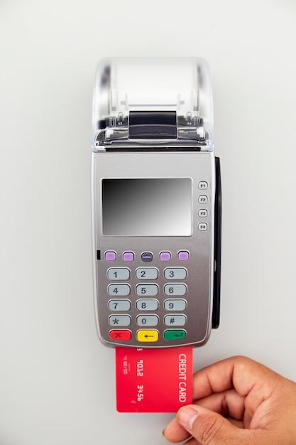 La mano maschile tiene in mano una carta di credito rossa sul terminale Foto Premium