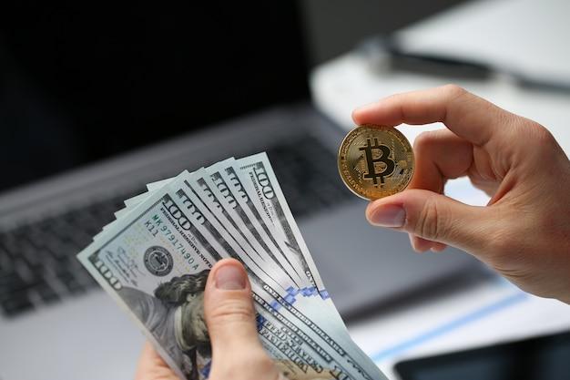 La mano maschio tiene bitcoin e moneta da un dollaro Foto Premium