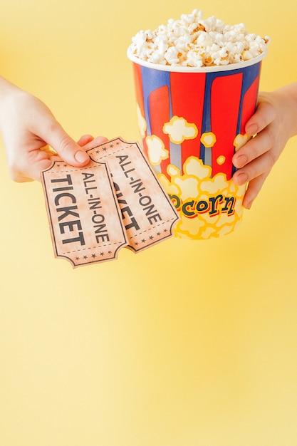 La mano prende biglietti per un film e popcorn da un bicchiere di carta Foto Premium