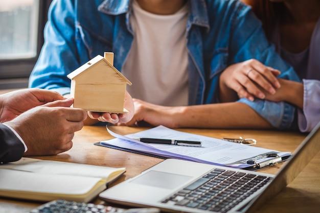 La mano rappresentativa di vendita del primo piano offre il modello di legno della casa alle giovani coppie asiatiche Foto Premium