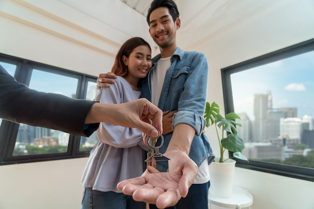 La mano rappresentativa di vendita del primo piano offre la catena chiave della casa alle giovani coppie asiatiche Foto Premium