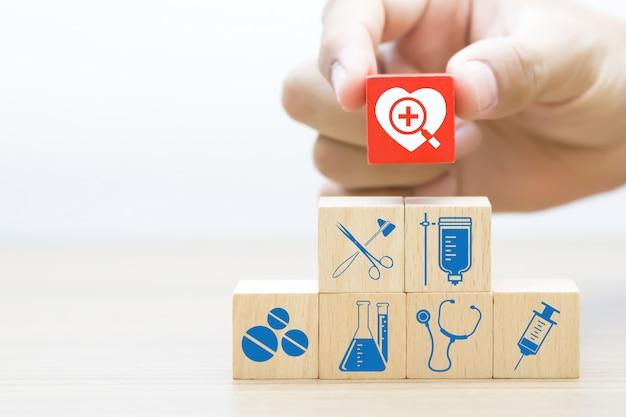 La mano sceglie il blocco di legno con l'icona medica e sanitaria. Foto Premium