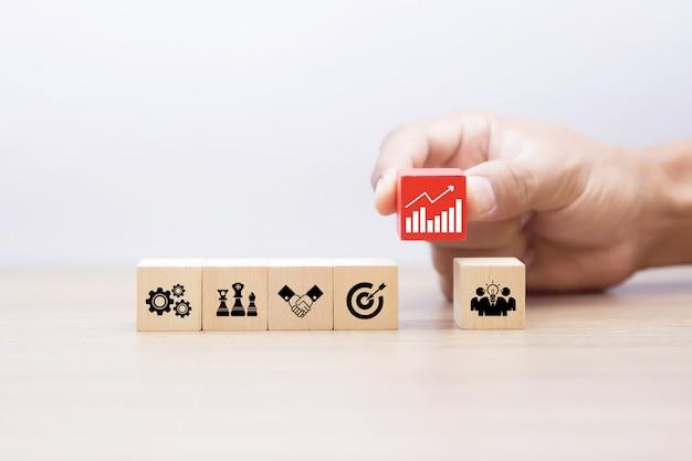 La mano sceglie il blog di legno con le icone del grafico commerciale Foto Premium