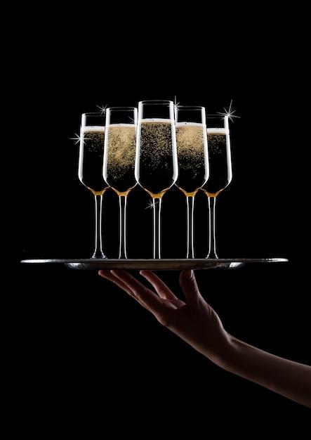 La mano tiene il vassoio con bicchieri di champagne gialli Foto Premium