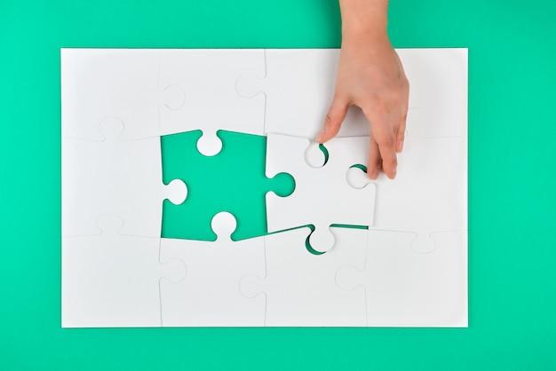 La mano tiene l'elemento mancante nel gioco dei puzzle su un verde Foto Premium