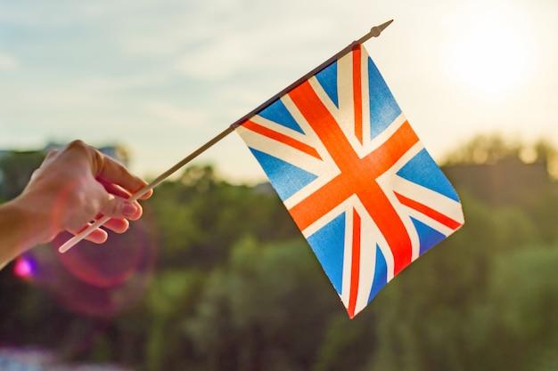 La mano tiene la bandiera della gran bretagna in una finestra aperta Foto Premium