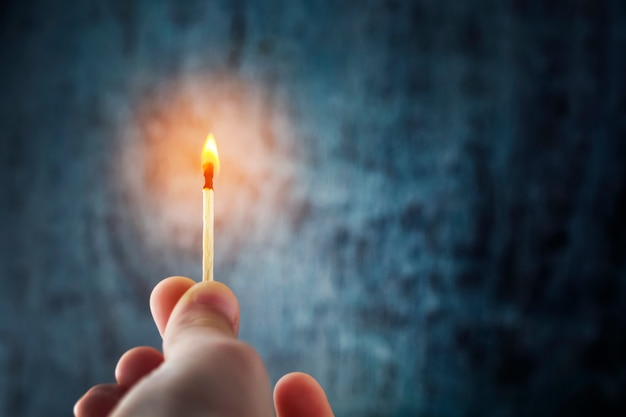 La mano tiene un fiammifero, illumina l'oscurità con la fiamma. Foto Premium