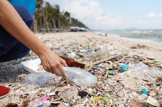 La mano turistica volontaria pulisce i detriti di plastica e dell'immondizia sulla spiaggia sporca nella grande borsa blu Foto Premium
