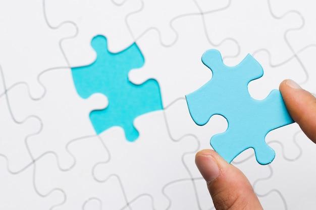 La mano umana che tiene il puzzle blu collega sopra il fondo bianco di griglia di puzzle Foto Gratuite